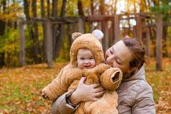 有婴孩的妇女胳膊的,摆在秋天公园 免版税图库摄影