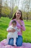 有婴孩的妈妈在桃红色格子花呢披肩的明亮的衣裳的在绿色右边 休息在公园的家庭在一温暖的天 库存照片