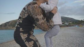 有婴孩的年轻母亲日落海滩的 黑紧的礼服的可爱的白种人妇女舒展手上升 影视素材