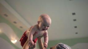 有婴孩的年轻母亲有游泳在户内水池享用 充满使用与小孩儿子的爱的愉快的妈妈在水池- 影视素材