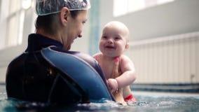 有婴孩的年轻母亲有游泳在户内水池享用 充满使用与红色的小孩儿子的爱的愉快的妈妈 影视素材