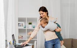 有婴孩的愉快的在家运转母亲和的膝上型计算机 免版税库存照片