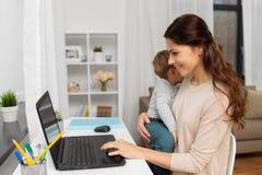 有婴孩的愉快的在家运转母亲和的膝上型计算机 免版税库存图片