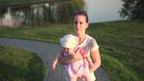 有婴孩的母亲在手上从湖,日落,橙色光去  股票视频