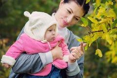有婴孩的母亲在秋天森林里 库存照片