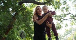 有婴孩的母亲有在背景绿色树的乐趣时间在公园,愉快的家庭休息 股票视频