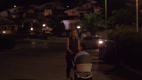 有婴孩的母亲有晚步行在街道 股票视频