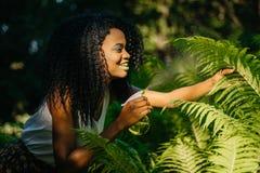 有嫉妒阴影和唇膏的可爱的微笑的非洲女孩为蕨使用绿色塑料触发器浪花 库存照片