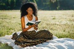 有嫉妒阴影的可爱的年轻非洲女孩读书在野餐期间在晴朗的草甸 免版税库存照片