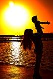 有子项的妇女日落的 免版税图库摄影