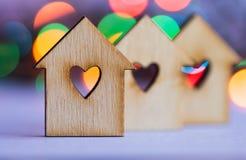 有孔的三个木房子以心脏的形式在五颜六色的bokeh的 图库摄影
