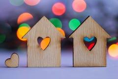 有孔的两个木房子以与一点hea的心脏的形式 免版税库存照片