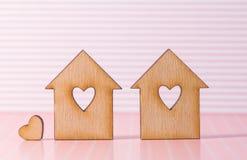 有孔的两个木房子以与一点hea的心脏的形式 库存照片