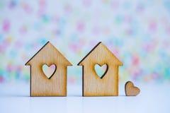 有孔的两个木房子以心脏的形式与一点心脏o的 免版税库存照片