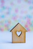 有孔的木房子以心脏的形式在五颜六色的背景的 库存图片