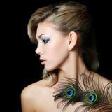 有孔雀的羽毛的美丽的妇女 免版税库存照片