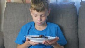 有字符的男孩 青少年的看看糖果和嗅到他们 不健康吃的概念 股票录像