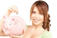 有存钱罐和硬币的可爱的十几岁的女孩 免版税库存照片