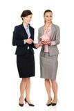 有存钱罐的两名女实业家 免版税库存图片