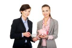 有存钱罐的两名女实业家 免版税库存照片