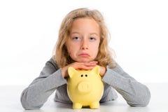 有存钱罐的女孩不是愉快的 库存图片