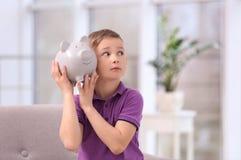 有存钱罐的小男孩 免版税库存照片