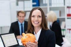 有存钱罐的成功的女实业家 免版税图库摄影