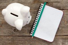 有存钱罐的空白的螺纹笔记本 免版税库存图片
