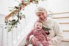 有孙女的祖母坐台阶在圣诞节 免版税库存照片