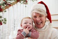 有孙女的祖母坐台阶在圣诞节 图库摄影