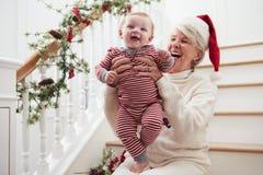 有孙女的祖母坐台阶在圣诞节 免版税库存图片