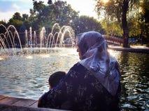 有孙子的祖母由喷泉池塘 免版税图库摄影