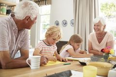 有孙的在厨房里,关闭微笑的祖父母 免版税库存照片