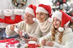 有孙的愉快的祖父母一起为圣诞节做准备 免版税图库摄影