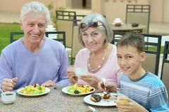 有孙的祖父母早餐的 免版税库存照片