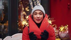 有孟加拉火的快乐的女孩在一个老冬天镇的街道上站立 股票视频