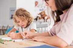 有孤独性光谱混乱的孩子和由一张桌图画的治疗师与在知觉期间的蜡笔 免版税图库摄影
