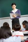 有学员的教师在中国学校教室 免版税库存图片