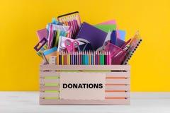 有学校和办公用品的箱子与在明亮的黄色背景的一个标志 捐赠概念 免版税库存照片