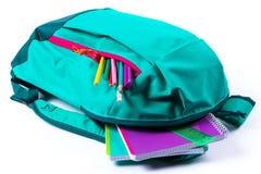 有学校文具的背包在白色背景 库存照片
