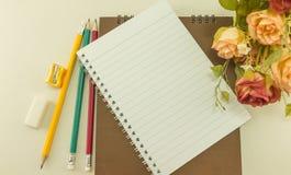 有学校用品的空白的笔记本和上升了,葡萄酒 免版税库存图片