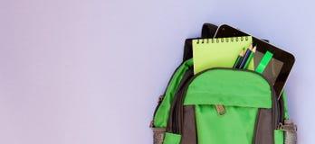有学校用品的背包在紫罗兰色backgriond 图库摄影