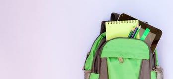 有学校用品的背包在紫罗兰色backgriond 库存照片