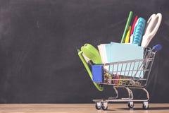 有学校用品的购物车在黑板背景 回到学校销售额概念 图库摄影
