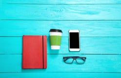 有学校辅助部件和智能手机的工作场所在蓝色木背景 顶视图和拷贝空间 免版税库存照片