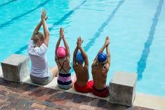 有学生的女性游泳辅导员在水池边 免版税图库摄影