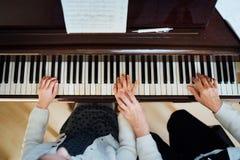有学生的音乐教师在教训钢琴, 免版税库存照片