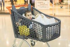 有孩子坐的产品的一辆台车 充分的推车用食物在超级市场 在推车坐婴孩 免版税库存照片