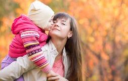 有孩子女孩室外秋天的美丽的妇女 孩子亲吻的mo 免版税库存图片