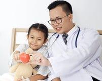 有孩子女孩患者的医生 免版税库存图片